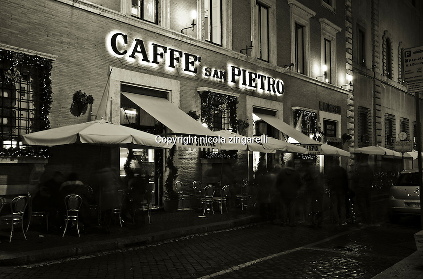 Caffé San Pietro with people outside at night. A typical bar near San Peter's square in Via della Conciliazione. Rome. Italy