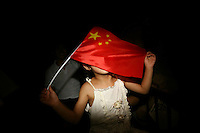 CHINA. Beijing. A young girl drapes the Chinese flag over her face whilst watching the opening ceremony of the Beijing Summer Olympics. 2008