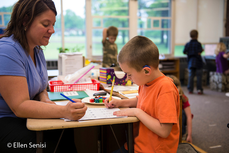 MR / Schenectady, NY. Zoller Elementary School (urban public school). Kindergarten inclusion classroom. Paraprofessional does assessment of kindergarten math skills for student (boy, 5, with hearing aid). MR: You6, Sch20. ID: AM-gKw. © Ellen B. Senisi.