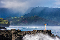 A woman standing on lava rocks lifts her arms while waves break around her, Hanalei Bay, Kaua'i.