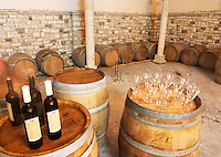 Oak barrels and bottles and glasses set up for a tasting. Cobo winery, Poshnje, Berat. Albania, Balkan, Europe.