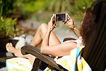 Young woman lying in a lounge chair in the sun, sunbathing with an iPhone in her hands, watching a movie on the phone screen