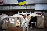 UKRAINE, Kiev, 30/05/2012.Une passante regarde une exposition organisée par le comité de soutien à Ioulia Timochenko dans le centre de Kiev, Ukraine. Quelques trente membres du comité de soutien de Ioulia Timochenko vivent dans un camp de tentes installées dans le centre de la ville depuis plus de 300 jours pour exprimer leur soutien à l'opposante politique Ukrainienne Ioulia Timochenko condamnée, le 11 octobre 2011 à sept ans d'emprisonnement pour abus de pouvoir dans le cadre de contrats gaziers signés avec la Russie en 2009, alors qu'elle exerçait la fonction de chef du gouvernement..UKRAINE, Kiev, 2012/05/30..A passant watching an exhibition organized by the committee to support Tymoshenko in the center of Kiev, Ukraine. Some thirty committee members support Tymoshenko living in a tent camp set up in the center of the city for more than 300 days to express their support for the Ukrainian opposition politician Yulia Tymoshenko sentenced October 11, 2011 seven years imprisonment for abuse of power through gas contracts signed with Russia in 2009, when she held the position of head of government..© Pierre Marsaut / Est&Ost Photography