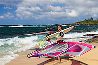 A windsurfer takes his windsurfing board out to the ocean at Ho'okipa Beach, Maui. (NOTE: the man in foreground model released, the others are not model released.)