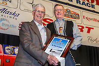 Dr. Terry Adkins (Left), the only veterinarian on the 1973 race recieves the Joe Redington Sr. Founder's Award from John Norman at the 2016 Iditarod musher position drawing banquet at the Dena'ina convention center in Anchorage, Alaska on Thursday March 3, 2016  <br /> <br /> © Jeff Schultz/SchultzPhoto.com ALL RIGHTS RESERVED<br /> DO NOT REPRODUCE WITHOUT PERMISSION