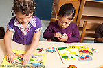 Education preschool 3 year olds two girls playing side by side with puzzles separately horizontal
