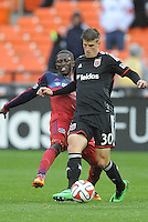 Washington, D.C.- March 29, 2014. Conor Doyle (30) of D.C. United shield the ball against Patrick Nyarko of the Chicago Fire. The Chicago Fire tied D.C. United 2-2 during a Major League Soccer Match for the 2014 season at RFK Stadium.
