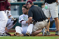 Mississippi State first baseman Wes Rea (35) with the training staff while sitting on the ground after a collision during Game 1 of the 2013 Men's College World Series Finals against the UCLA Bruins on June 24, 2013 at TD Ameritrade Park in Omaha, Nebraska. The Bruins defeated the Bulldogs 3-1, taking a 1-0 lead in the best of 3 series. (Andrew Woolley/Four Seam Images)