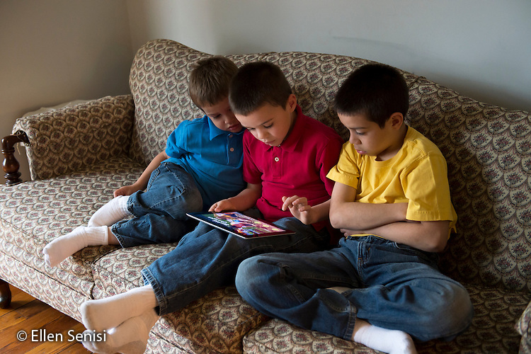 MR / Schenectady, New York. Young children (boys, brothers, 4,7,9) use iPad to read eBook / app at home. ID: AM-Gar. ©Ellen B. Senisi