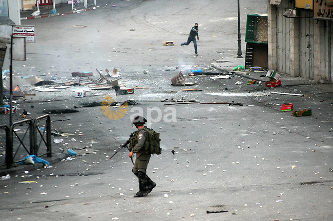A Palestinian man throws stones at Israeli soldiers during clashes in the West Bank city of Hebron, 13 March 2013, following the funeral of Mahmoud Adel al-Titi, 22, who was shot dead by an Israeli soldier during an Israeli military operation in al-Fawwar refugee camp on Tuesday. Photo by Mamoun Wazwaz