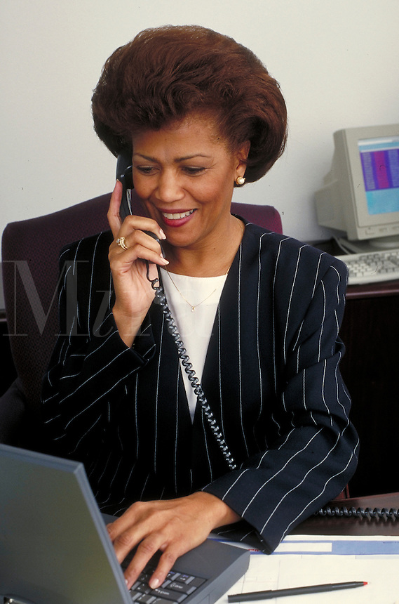 Woman conducting business, talking on the telephone while working on a laptop. Professionals. Businesswoman. African American. Ethnic. Denver Colorado USA.