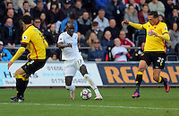 Modou Barrow of Swansea City (C) gets past Miguel Britos (L) and Jose Holebas of Watford during the Premier League match between Swansea City and Watford at The Liberty Stadium on October 22, 2016 in Swansea, Wales, UK.