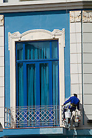 Worker painting a building facade on Prado Avenue, Havana, Cuba.