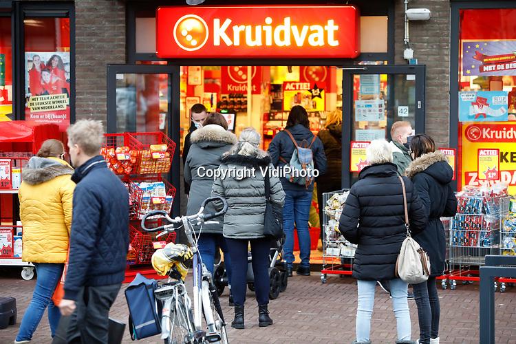 Foto: VidiPhoto<br /> <br /> ELST – Topdrukte in de winkels maandag na de bekendmaking dat de niet-essentiële retail vanaf dinsdag dicht moet. Niet alleen in de grote steden, maar ook in kleinere plaatsen zoals hier in Elst Gelderland, gingen inwoners nog even snel naar de winkel om de laatste inkopen te doen. Vooral boekwinkels en drogisterijen profiteerden flink van de massale toestroom, waardoor er buiten lange wachtrijen ontstonden.