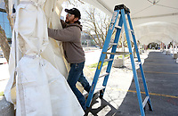 Kenneth Fensom, with Intents Party Rentals, assembles the side walls for a marquee tent Thursday, April 1, 2021, in the parking lot of the Walton Arts Center in Fayetteville. The tents are for the Pop Up Lounge hosted by Experience Fayetteville taking place Friday night and all day and night Saturday. The lounge is encouraging patrons to purchase and bring meals and outdoor refreshments from downtown merchants and restaurants and enjoy the space that will feature a live music and a rainbow canopy.Check out nwaonline.com/210402Daily/ and nwadg.com/photos for a photo gallery.<br /> (NWA Democrat-Gazette/David Gottschalk)