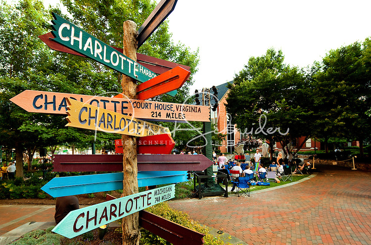 """Photo of the iconic Charlotte signs statue/public art located on The Green in Uptown Charlotte. The Green, actually the top level of an underground parking garage, is a tiered outdoor space with a lawn, lush gardens, interactive fountains and abundant public art. Contemporary artist Gary Sweeney, based in San Antonio, created the piece named """"Charlotte - The Center of the Known World."""" The signs point to 11 other areas also named Charlotte. The signs point to the approximate direction of the locales they identify and the distance to each. Photo taken during the 2012 Charlotte Shakespeare Festival. .."""