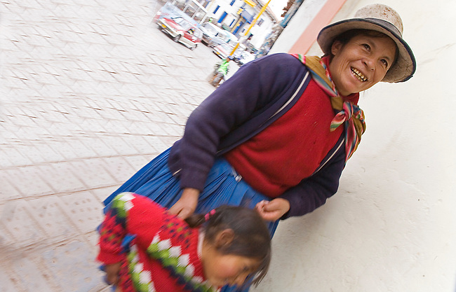 A SMILING MOTHER ATTENDS TO HER DAUGHTER IN THE STREETS OF CUZCO,PERU