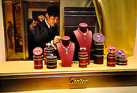 Luxury shopping: adjusting a display in the window of Cartier.