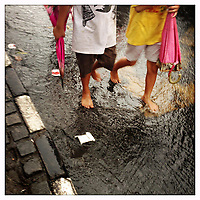Children walk through flooded street sin the city of Jakarta, Indonesia.