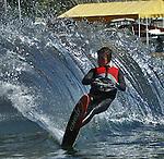 Water skier sprays a huge wall of water.