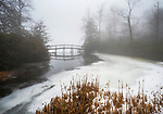 Outlet pond walk bridge, Eagles Mere, PA. in winter snow, ice, and fog.