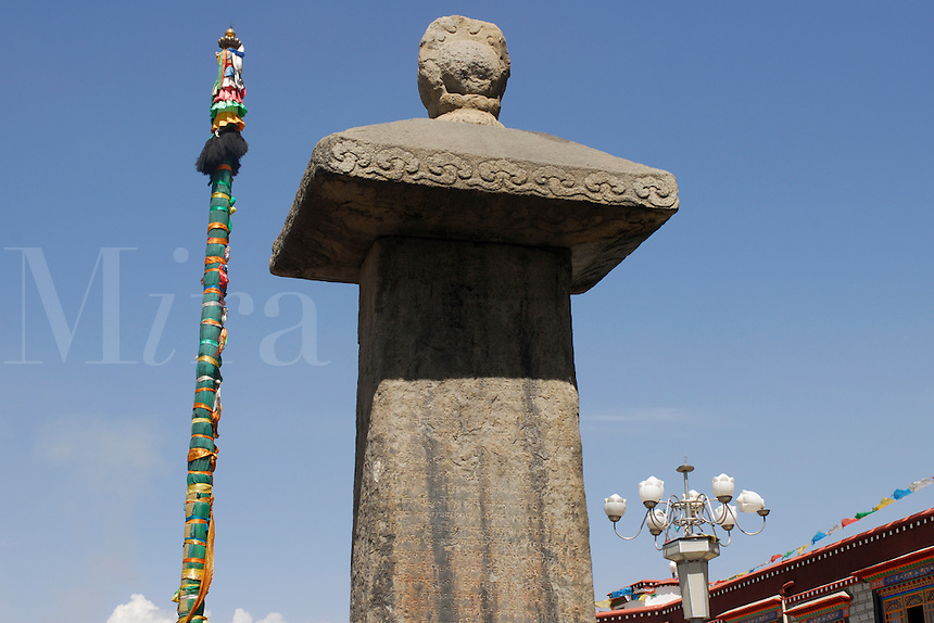 Traditional Buddhist prayer-flag pole, ancient 822 A.D. stone stele inscribed with  Sino-Tibetan peace treaty, and modern Chinese lights, in front of 7th century Jokhang Temple, Lhasa, Tibet.