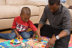 2 year old toddler boy with father interaction language development interacting with counting number puzzle and toys horizontal African American