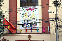 Vietnam. Hanoi. Police station in the town's center. Poster celebrating the communist victory with the figure of Ho Chí Minh (May 19, 1890 - September 2, 1969) who was a Vietnamese Communist revolutionary and statesman as Prime Minister (1946-1955) and President (1946-1969) of the Democratic Republic of Vietnam (North Vietnam). Ho Chí Minh led the Viet Minh independence movement from 1941 onward, establishing the communist-governed Democratic Republic of Vietnam in 1945 and defeating the French Union in 1954. He lost political power inside North Vietnam in the late 1950s, but remained as the highly visible figurehead president until his death. The flag of Vietnam, also known as the red flag with yellow star. The red symbolises the revolution and the blood shed in the struggle for independence. The five-pointed yellow star represents the unity of workers, peasants, intellectuals, traders and soldiers in building socialism 08.04.09 © 2009 Didier Ruef