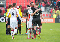 Toronto, Ontario - May 3, 2014: New England Revolution midfielder Andy Dorman #12 and Toronto FC defender Steven Caldwell #13 embrace at the end of a game between the New England Revolution and Toronto FC at BMO Field.<br /> The New England Revolution won 2-1.