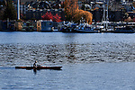Kayaker passes by houseboat community on Lake Union in Seattle, Washington in photo from Gasworks Park.