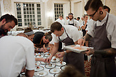 Charleston, South Carolina<br /> October 24, 2013<br /> <br /> 17 internationally renowned chefs, attending the Cook It Raw event in Charleston, put the final touches on plates and serve them to a select crowd for dinner at McCrady's restaurant.<br /> <br /> Sasu Laukkonen (back to camera bending down on the left) owner, chef and sommerier at restaurant Eira in Helsinki, Findland, and chef Brandon Baltzley (in focus center) from restaurant TMIP in Laporte County, Indiana (center) work on the final touches of a plate. Chef James Lowe from the restaurant The Young Turks in London, England is bent down middle on the right.
