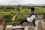A young artist with scrolls of paintings, looks out over the pagodas of  Bagan, waiting for another group of tourists to arrive.   SHWE-SAN-DAW TEMPLE. LOOKING TOWARDS ANANDA TEMPLE. BAGAN Myanmar South East Asia 2006 ( Burma )