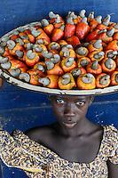 SIERRA LEONE Tombo , girl sells cashew nut and fruit on plate at the market / SIERRA LEONE Fischerhafen Tombo, Maedchen verkauft Kaschu Nuesse mit Kaschufrucht