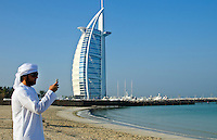 Emirate arab man with cell phone texting in front of Worlds only 7 star hotel in Dubai UAE called the Burj Al Arab with luxury and water  at beach in United Arab Emirates