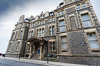 Pictured: The old Police Station in Aberystwyth, Wales, UK. Wednesday 28 August 2019<br /> Re: Opened 1866, built by the Hafod Hotel Co as the Queens Hotel; architects, Hayward and Davies; builder George Lumley of Aberystwyth. Sold in 1877 and later converted to local government use; remodelled in1950 by G R Bruce, County Architect.<br /> Detached towards N end of the Promenade, with main entrance to side elevation in Albert Place and rear elevation to Queens Road.<br /> Hotel de Ville style. Asymmetrical 3-storey attic and basement snecked rubble 13-bay W (Promenade) elevation; stepped front with mostly vermiculated dressings, stock brick voussoirs, deep entablature and cornice and cill bands; buttresses to ground floor centre. Steep pitch mansard slate roof with truncated chimney stacks. Dormers with steep overhanging roofs and casement windows; paired to left. 3-bays advanced near the right hand end and with additional storey and splayed angles to 2nd floor (with small cast-iron parapets) and 3rd floor; also to top floor) with small cast-iron parapets) and 3rd floor; also to top floor at the corner. Sash windows, some paired; anthemion panelled cast-iron window box holder across central bays.