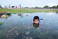 A young boy swims in a flooded area near the airport runway, in downtown Funafuti. Parts of the island flood at this time of the year due to the 'king tides'. The king tides are seasonal and are characterised by very high water levels in the surrounding ocean. At this time of year the waves inundate the coastline but also water seeps up through the ground which is made of porous coral. This natural phenomenon is particularly serious for Tuvalu, a low-lying atoll island nation, whose highest point is only a few metres above sea level. As sea levels rise, the king tides regularly flood parts of the island and will likely increase in severity in the future, potentially making large parts of the nation uninhabitable. Funafuti, Tuvalu. March, 2019.