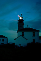 The light is cast during a peaceful evening sunset at Beavertail Lighthouse