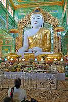 Myanmar, Burma.  Buddha Statue and Worshiper, near Mandalay.  Soon U Ponya Shin Pagoda, Sagaing Hill.