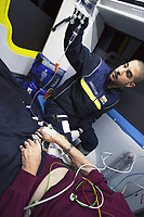 Switzerland. Canton Ticino. Pregassona. A senior man lying down on an emergency medical stretcher is brought to hospital for medical examination. The elderly man is suffering from a heart problem. The paramedic, wearing a blue uniform and medical gloves, is a volunteer specifically trained in emergency rescue. He checks the patient's intravenous infusion of saline solution. The patient is also connected to a monitor which controls a set of vital functions, such as  electrocardiogram, blood pressure's measurement, respiratory rate and pulse oximetry (oxygen saturation). TheCroce Verde Lugano is a private organization which ensure health safety by addressing different emergencies services and rescue services. TheCroce Verde Lugano is a private organization which ensure health safety by addressing different emergencies services and rescue services. Volunteering is generally considered an altruistic activity where an individual provides services for no financial or social gain to benefit another person, group or organization. Volunteering is also renowned for skill development and is often intended to promote goodness or to improve human quality of life. Medical gloves are disposable gloves used during medical examinations and procedures to help prevent cross-contamination between caregivers and patients. Medical gloves are made of different polymers including latex, nitrile rubber, polyvinyl chloride and neoprene. Pregassona is a quarter of the city of Lugano. 20.01.2018 © 2018 Didier Ruef
