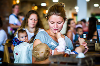 Mothers who have come together to celebrate the annual Big Latch On breastfeeding promotion event breastfeeding in a cafe. The baby puts its finger in the mum's mouth while feeding.Dorset, England, UK<br /> <br /> 02/08/2014<br /> <br /> <br /> © Paul Carter / wdiip.co.uk