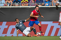 Orlando, Florida - Saturday, June 04, 2016: Paraguayan forward Paulo Da Silva (14) slide tackles to win possession from Costa Rican forward Marco Urena (21) during a Group A Copa America Centenario match between Costa Rica and Paraguay at Camping World Stadium.