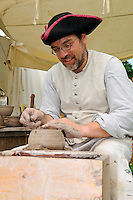 Colonial potter trims the base of a spinning pot to the correct flatness and thickness, on a foot-operated wheel, at the Nathan Hale Homestead during a Revolutionary War encampment and muster, Coventry, Connecticut, USA.