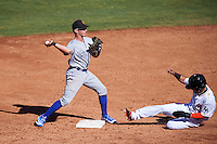 Surprise Saguaros Corey Toups (2), of the Kansas City Royals organization, throws to first as Yefri Perez (1) slides into second base during a game against the Mesa Solar Sox on October 14, 2016 at Sloan Park in Mesa, Arizona.  Mesa defeated Surprise 10-4.  (Mike Janes/Four Seam Images)