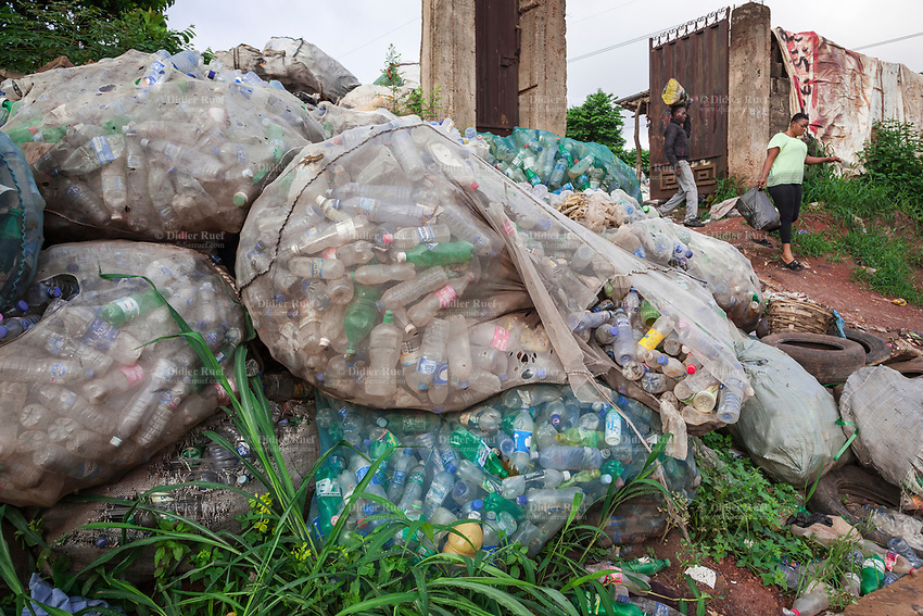 Nigeria. Enugu State. Enugu. Plastic waste picked-up by garbages collectors on garbage heap. A man and woman, both Igbo, walk out of the recycle depot. The plastic bottles will later be sold and used in the plastic industry. Enugu is the capital of Enugu State, located in southeastern Nigeria. 2.07.19 © 2019 Didier Ruef