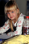 Ostrava, Czech Republic. Young blond girl with pencil and soft drink bottle.
