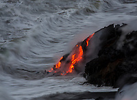 Waves collide with lava flowing into the ocean by Hawai'i Volcanoes National Park and the Kalapana border, Big Island.