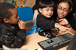 Preschool 3-4 year olds female teacher in training or therapist working with boy on computer horizontal