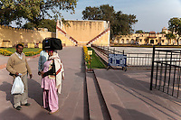 Jaipur, Rajasthan, India.  Jantar Mantar, an 18th-century Site for Astronomical Observations, now a World Heritage Site.  Indian Visitors, Woman Carrying her Suitcase on her Head.