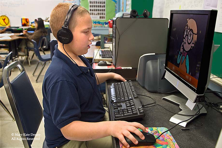 Autistic Caucasian second grade boy in school uniform wears headphones and works on a computer with a LCD monitor in classroom