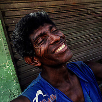 An Afro-Colombian carrier smiles after finishing a whole day work shift at the market of Bazurto in Cartagena, Colombia, 15 April 2018.